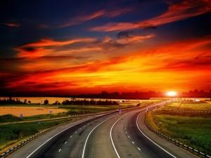 Postal: Puesta de sol sobre una carretera