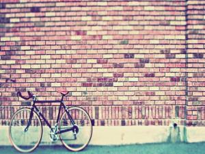 Postal: Bicicleta en una pared de ladrillo