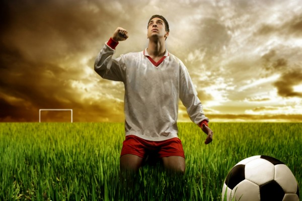 Futbolista arrodillado en un campo de fútbol