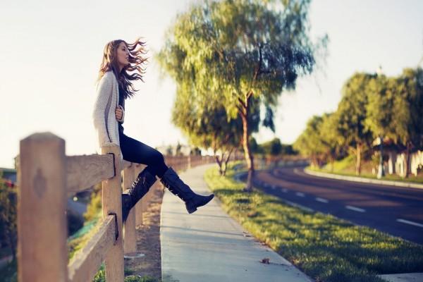 Chica sentada en una valla de madera