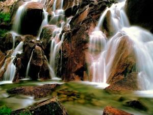 Postal: El cauce de un río sobre unas grandes rocas
