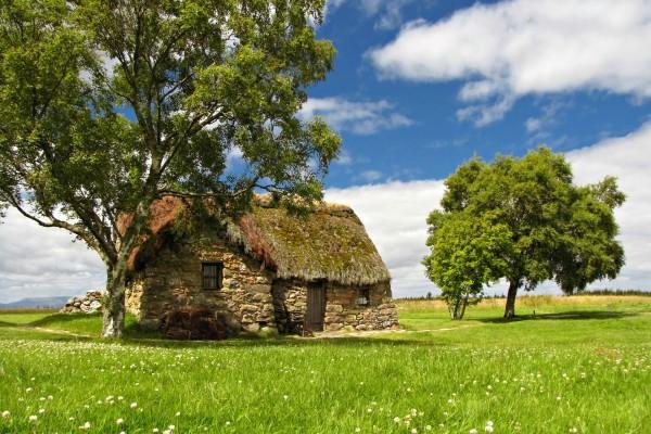 Cabaña de piedra en un prado verde