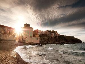 Sol brillando entre las casas de un pueblo costero