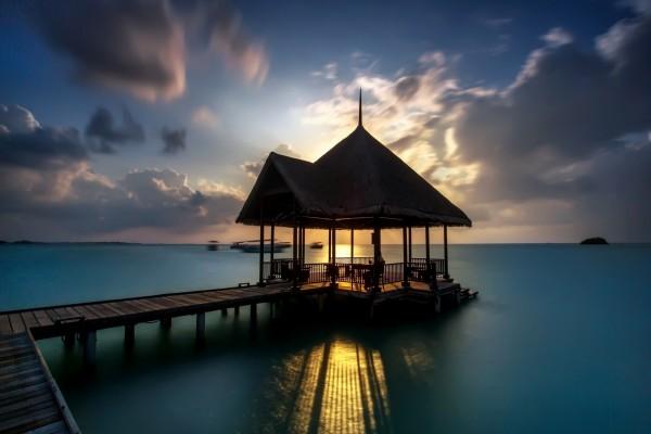 Contemplando el amanecer desde un muelle sobre el mar