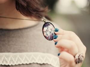 Postal: Chica sosteniendo un colgante