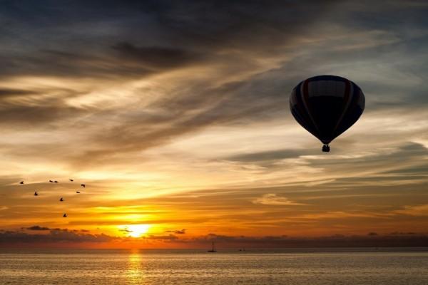 Globo volando sobre el mar al amanecer