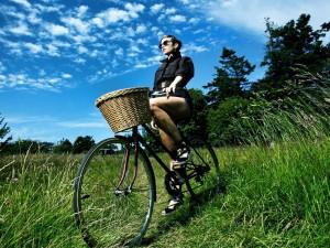 Chica paseando en bicicleta sobre la hierba fresca