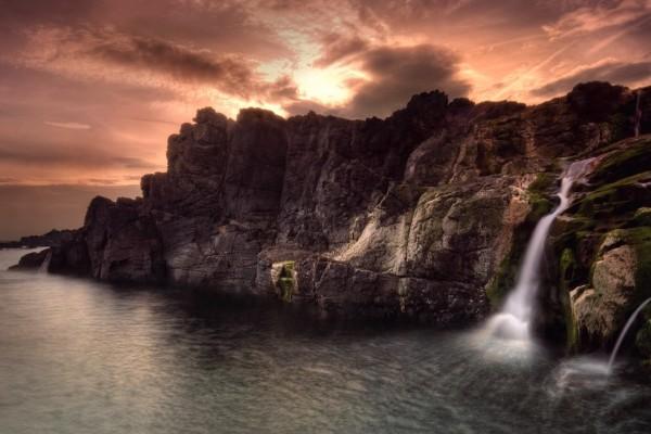 Cascada entre las rocas del mar