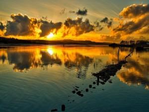 Sol y nubes reflejados en el agua