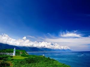 Faro blanco en la costa verde