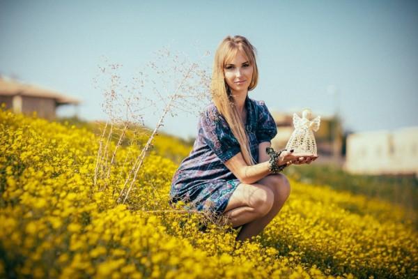 Chica en un campo de flores sosteniendo la figura de un ángel