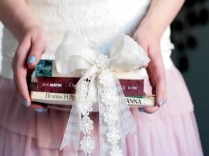 Sosteniendo tres libros atados con un lazo