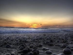 Postal: Playa cubierta de piedras oscuras