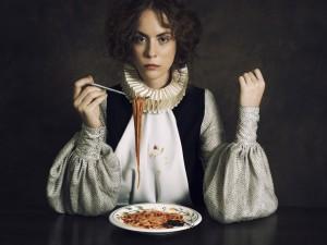 Mujer comiendo tallarines con tomate