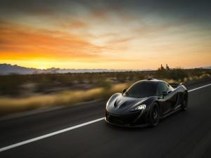 McLaren P1 circulando por una carretera al amanecer