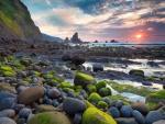Contemplando el amanecer desde una playa pedregosa