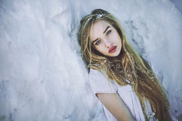 Chica tumbada sobre la fría nieve
