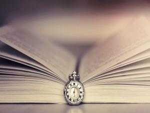 Postal: Reloj junto a un libro abierto