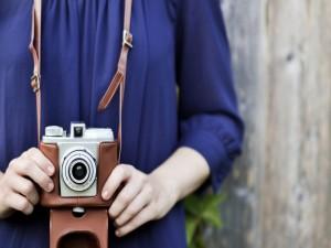 Postal: Cámara de fotos colgando del cuello de una joven