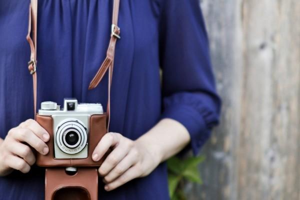 Cámara de fotos colgando del cuello de una joven