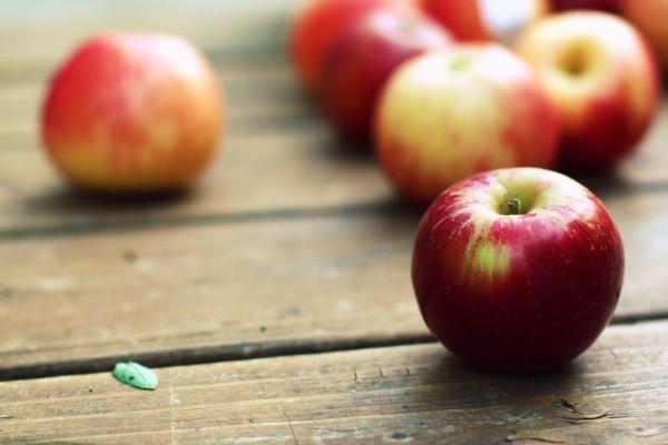 Pequeñas manzanas rojas sobre una mesa de madera