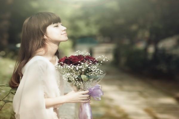 Mujer aspirando el aroma de las flores