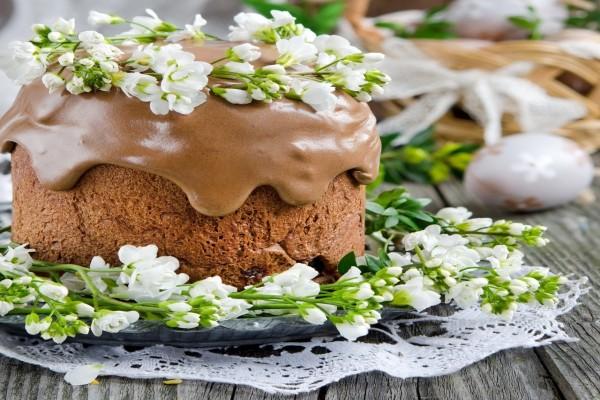 Pastel glaseado con chocolate y adornado con flores primaverales