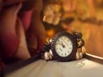 Reloj en una pulsera junto a unas perlas