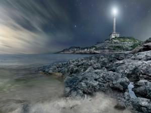 Faro iluminando una noche estrellada