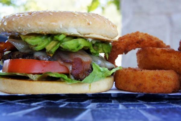 Aros de cebolla junto a una hamburguesa