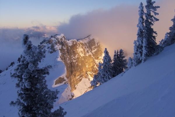 Sol iluminando una montaña nevada