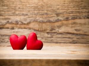 Dos corazones de madera pintados de rojo pasión