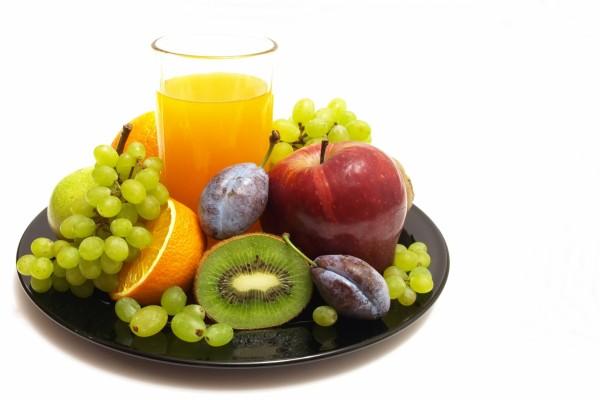 Vaso de zumo entre frutas frescas