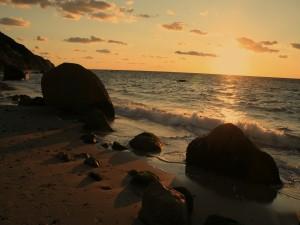 Postal: El sol iluminando la orilla del mar al amanecer