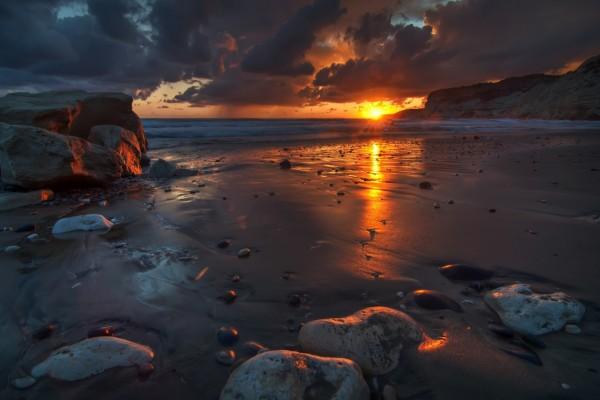 El sol del amanecer reflejado en la arena de una playa