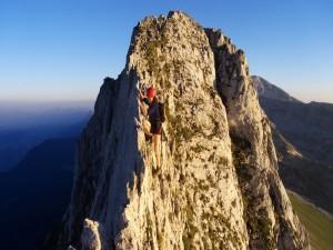 Postal: Mujer en lo alto de una cresta rocosa