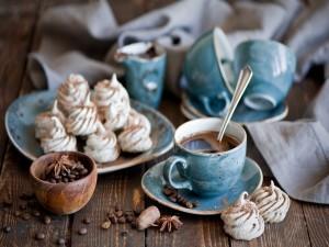 Postal: Taza de café especiado junto a pequeños merengues