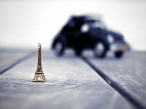 Pequeña torre Eiffel y un coche sobre un suelo de madera