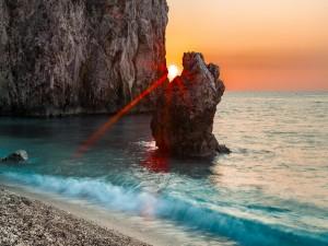 Postal: Rayos de sol entre dos rocas marinas