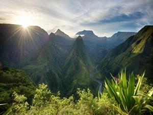 El sol iluminando las verdes montañas