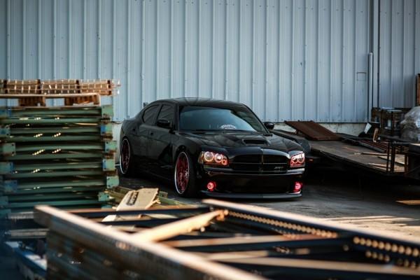 Un coche negro entre palets de madera
