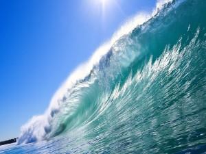 El sol iluminando una gran ola