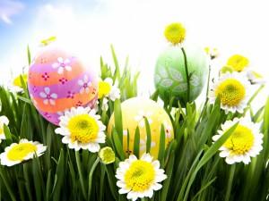 Decorativos huevos de Pascua entre la hierba y las flores