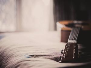 Guitarra sobre una cama