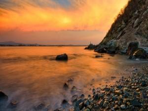 El sol entre las nubes visto desde una playa rocosa