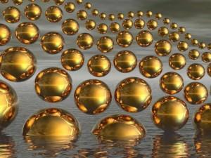 Múltiples esferas de color dorado emergiendo del agua
