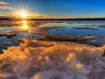 Los rayos dorados del sol iluminan un lago helado al amanecer