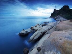 Hombre sentado en unas rocas contemplando el mar
