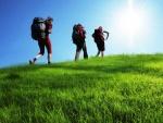 Tres mochileros caminando sobre una pradera verde
