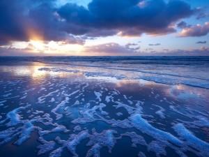 Amanecer reflejado en la orilla de una playa